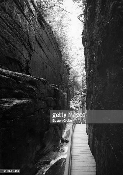Tourists walk up the staircase lining the Flume Gorge a natural gorge extending 800 feet at the base of Mount Liberty in Franconia Notch State Park...