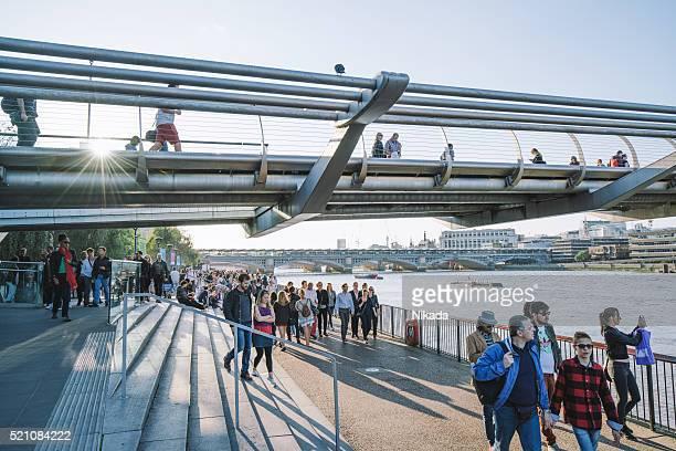 Tourists walking along the Millenium Bridge in London, UK