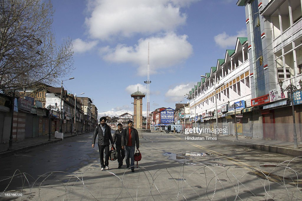Tourists walking near barbed wire during a curfew on March 15, 2013 in Srinagar, India. Curfew continued for the second consecutive day in Srinagar district following the alleged firing by CRPF personnel on Wednesday in which a youth was killed. CRPF personnel allegedly opened fire after coming under attack by a group of stone pelters while on their way to hospital to donate blood for their colleagues injured in terror attack.