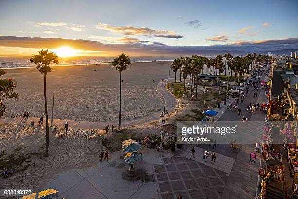 Tourists walking on footpath by beach during sunset