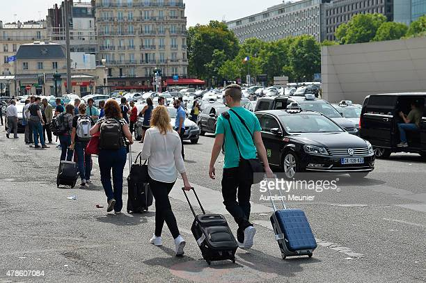 Tourists walking on the Porte Maillot square while French taxis drivers on strike for the second day protest against the UberPOP application on June...