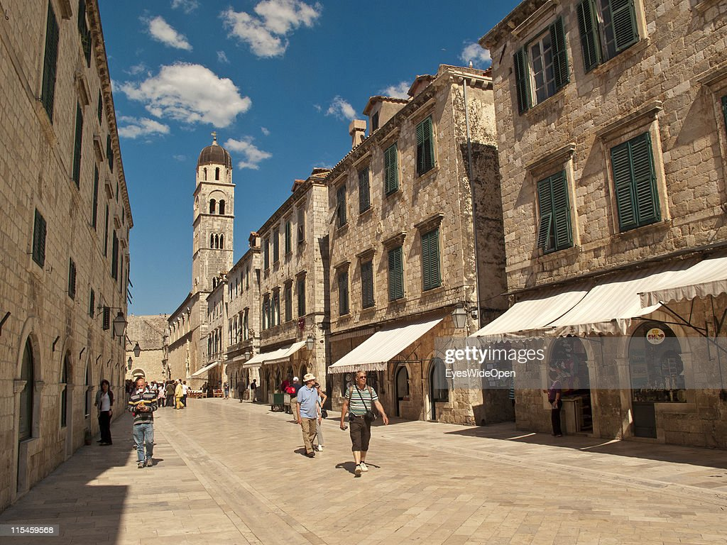 Tourists walking on the Stradun, the main street inbetween ancient monuments and restored buildings of the UNESCO World Heritage Site city of Dubrovnik on the Dalmatian coast of the Adriatic Sea on May 13, 2011 in Dubrovnik, Croatia. The old town is surrounded by a 1,9 km long city wall and called the Pearl of the Adriatic.