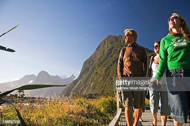 Tourists walking through Milford Sound with Mitre Peak in background.