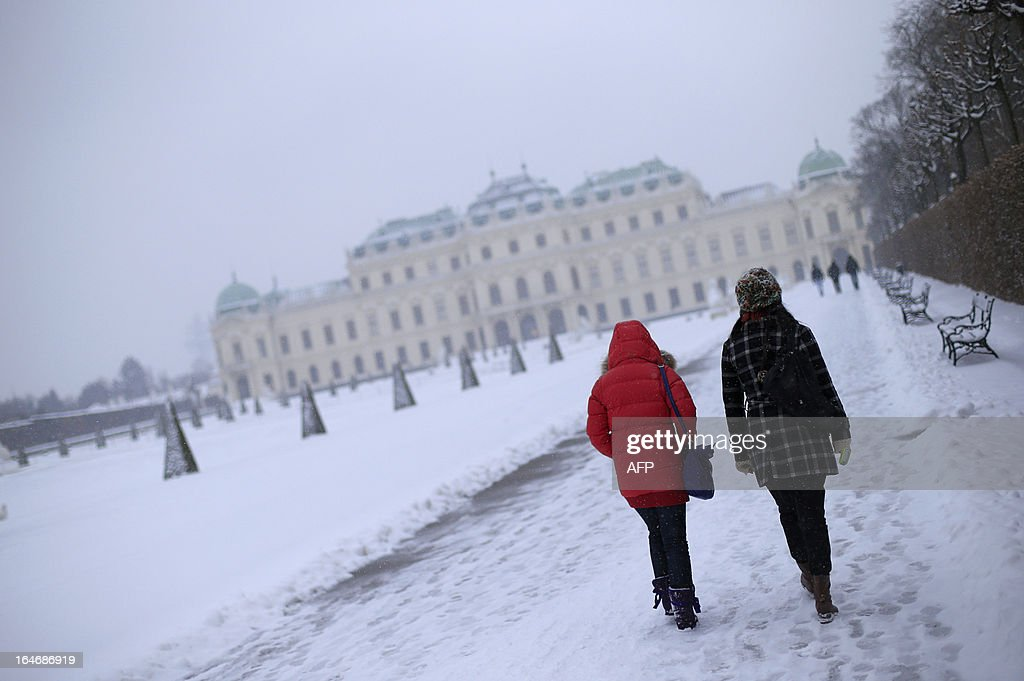 Tourists walks in the gardens of the Belvedere Palace on a snowy day in Vienna on March 26, 2013.