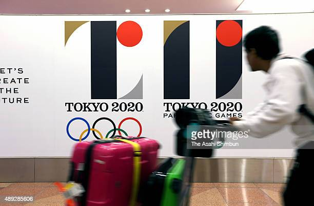 Tourists walks past posters of the withdrawn Tokyo 2020 Olympic and Paralympic Games emblems at Haneda International Airport on September 2 2015 in...
