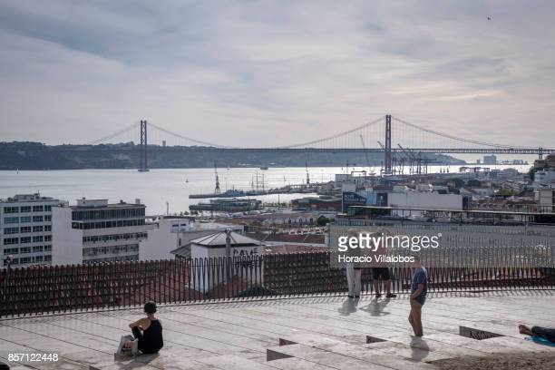 Tourists watch 25 de Abril bridge from the viewpoint of Santa Catarina a spot favored by visitors on October 01 2017 in Lisbon Portugal Although...