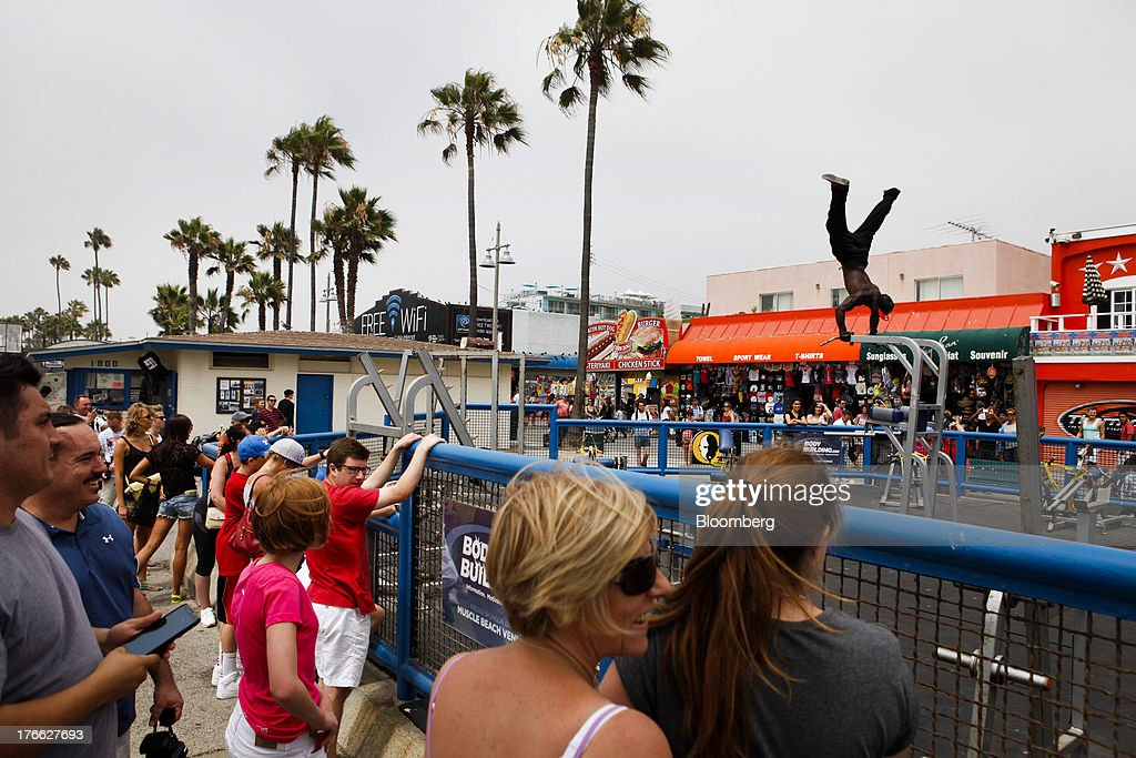 Tourists watch a bodybuilder perform an aerial workout at the Muscle Beach gym on Venice Beach in Los Angeles, California, U.S., on Wednesday, Aug. 14, 2013. Overall U.S. tourism-related sales increased 6.8% in the second quarter of 2013 as compared to 2012. Photographer: Patrick T. Fallon/Bloomberg via Getty Images