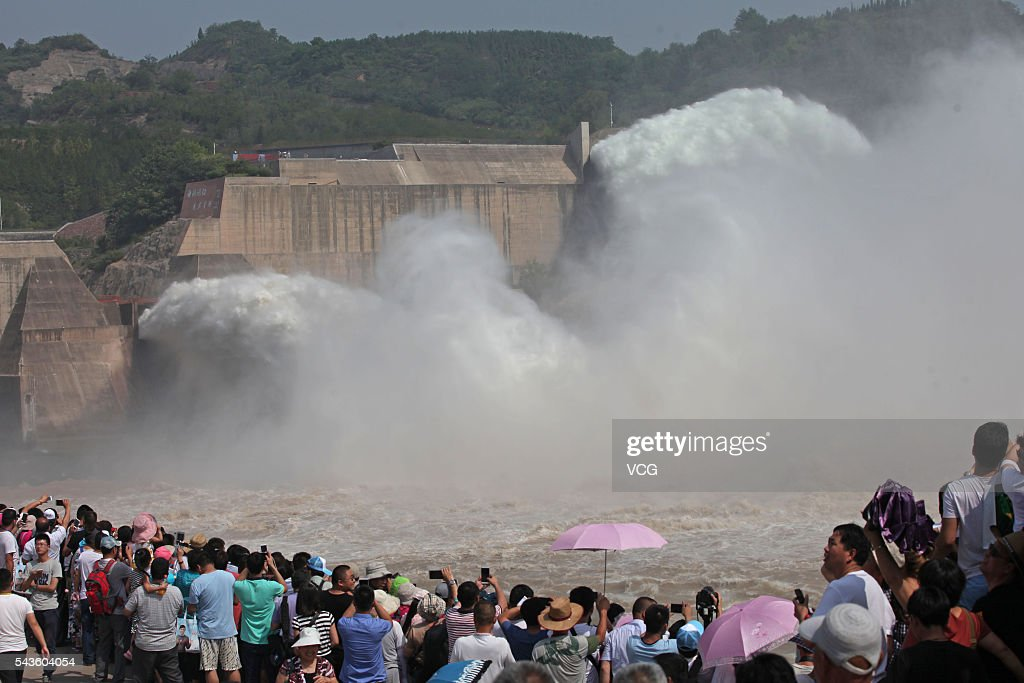 Tourists watch and take photos of water and sediment regulation at Xiaolangdi Dam on the Yellow River on June 29, 2016 in Luoyang, Henan Province of China. The water and sediment regulation is to let sand, silt and other sediment rush with water out of the dam and flow into sea. The regulation can increase the dam's capacity of flood storage.