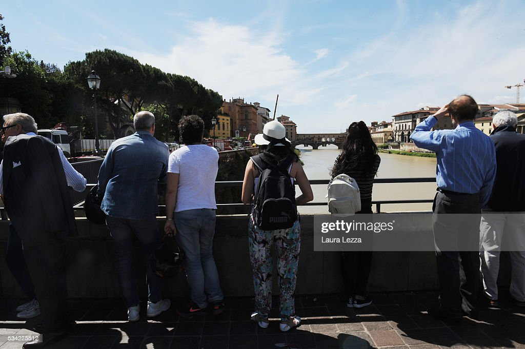 Tourists watch as a road collapsed along the Arno river on May 25, 2016 in Florence, Italy. The deterioration of one or more water pipes opened a 200 m wide and 7m deep hole on Wednesday morning along the bank of the river Arno close to the famous Ponte Vecchio bridge. Many cars that were parked sunk and damages are thought to be around 5 millions euros.