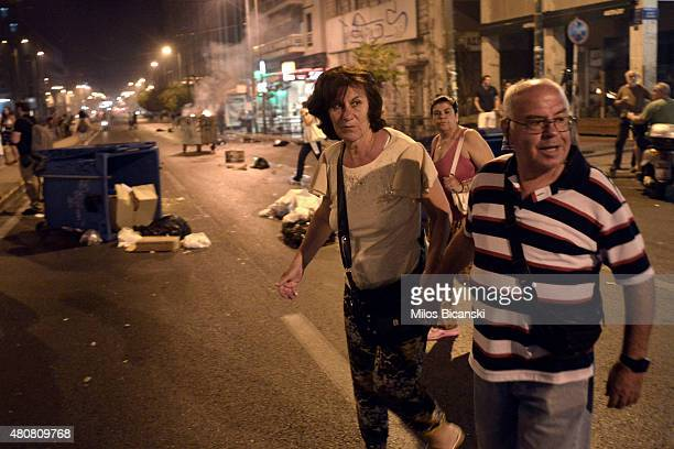 Tourists watch as debris burns on the streets following clashes between protestors and riot police on July 15 2015 in Athens Greece Antiausterity...