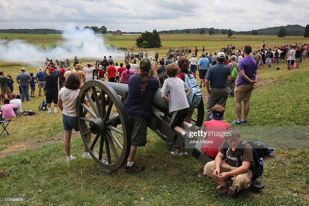 Tourists watch Confederate Civil War reenactors fire a cannon on the 150th anniversary of the historic Battle of Gettysburg on July 2 2013 in...