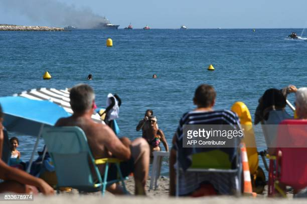 Tourists watch from afar as smoke rises from the boat 'If Only' a 39meterlong yacht that is on fire off SaintLaurentduVar near Nice southern France...