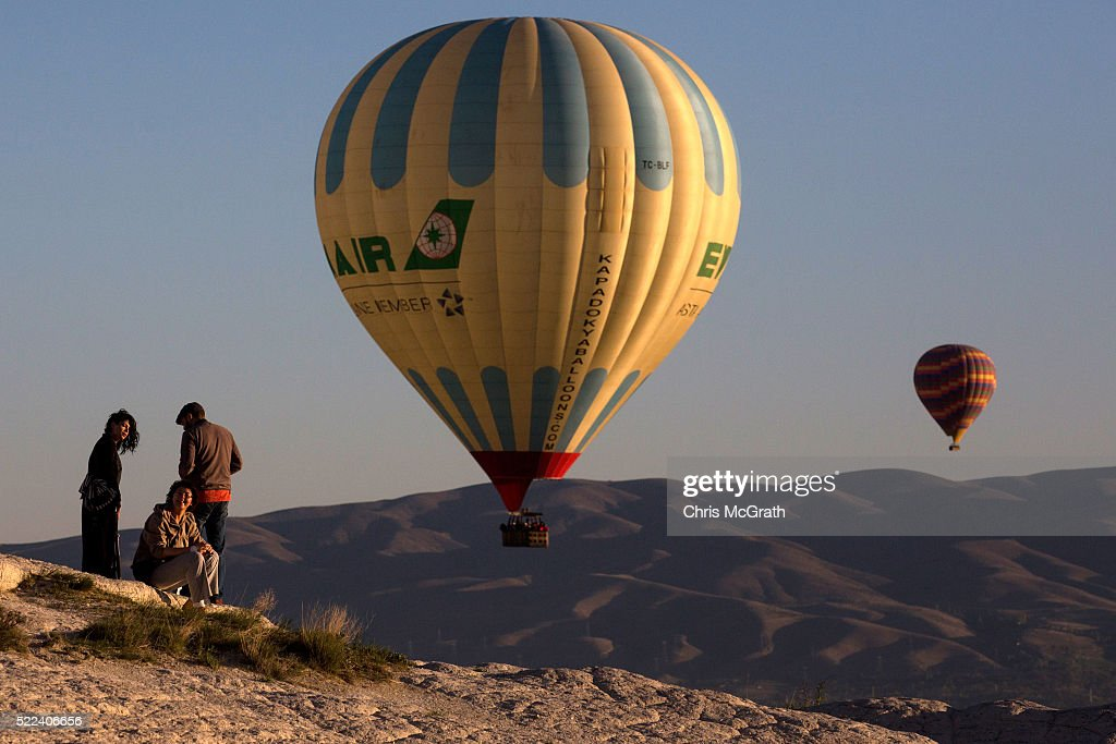 Tourists watch hot air balloons from a ridge in the town of Goreme on April 17, 2016 in Nevsehir, Turkey. Cappadocia, a historical region in Central Anatolia dating back to 3000 B.C is one of the most famous tourist sites in Turkey. Listed as a World Heritage Site in 1985, and known for its unique volcanic landscape, fairy chimneys, large network of underground dwellings and some of the best hot air ballooning in the world, Cappadocia is preparing for peak tourist season to begin in the first week of May. Despite Turkey's tourism downturn, due to the recent terrorist attacks, internal instability and tension with Russia, local vendors expect tourist numbers to be stable mainly due to the unique activities on offer and unlike other tourist areas in Turkey such as Antalya, which is popular with Russian tourists, Cappadocia caters to the huge Asian tourist market.