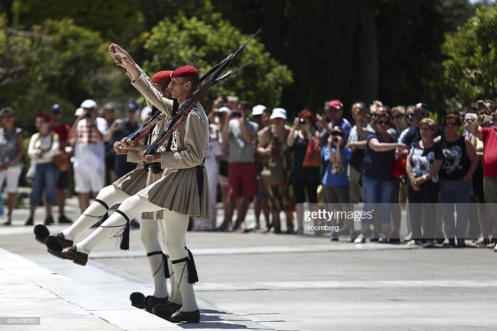 Tourists watch presidential guards perform their ceremonial duties on Syntagma Square in Athens, Greece, on Thursday, May 26, 2016. Greece may have passed a milestone and its bond market has been lucrative for some investors, but the road to recovery doesn't look much shorter. Photographer: Yorgos Karahalis/Bloomberg via Getty Images