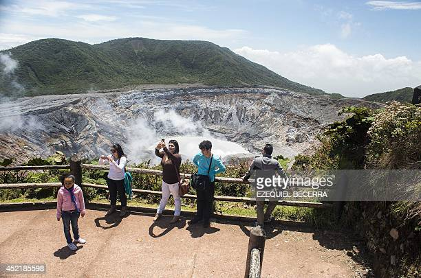 Tourists watch the crater of the Poas volcano at the Poas Volcano National Park 50km from San Jose on July 4 2014 Costa Rica hopes to capitalize for...