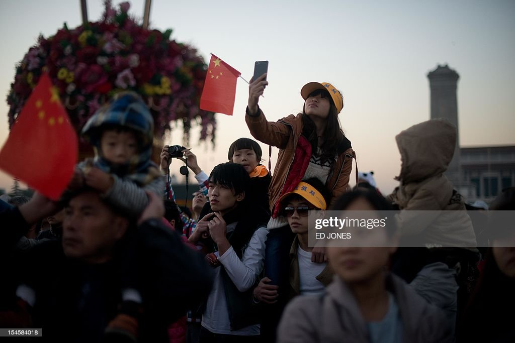 Tourists watch the daily flag-raising ceremony on Tiananmen Square early on October 23, 2012. Supporters of disgraced politician Bo Xilai have published a letter on a leftist website urging him not to be expelled from China's parliament which would pave the way for him to face trial over alleged corruption and charges. AFP PHOTO / Ed Jones