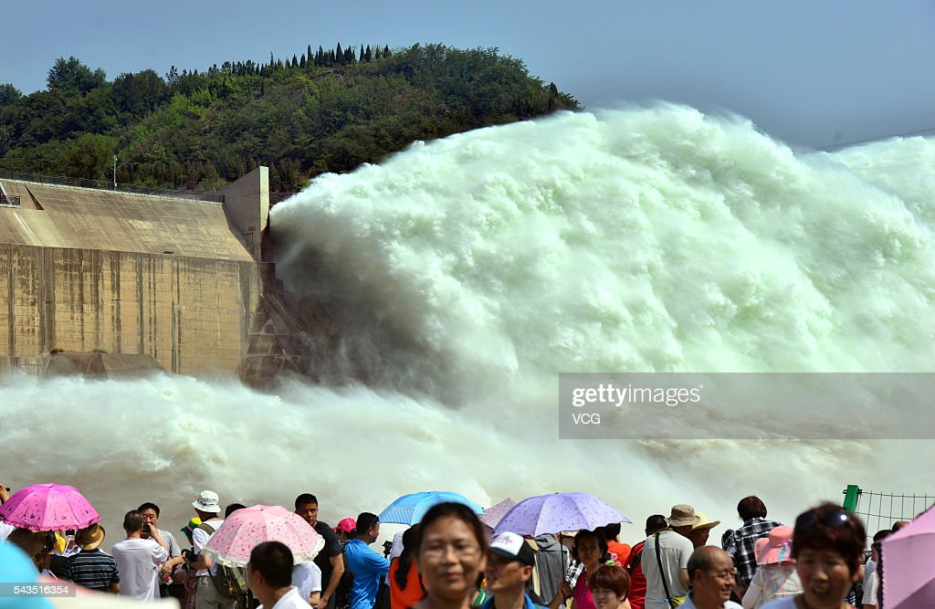 Tourists watch the effects of water and sediment regulation at Xiaolangdi Dam on the Yellow River on June 29, 2016 in Luoyang, Henan Province of China. The water and sediment regulation is to let sand, silt and other sediment rush with water out of the dam and flow into sea. The regulation can increase the dam's capacity of flood storage.