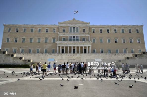 Tourists watch the presidental guards at the monument of the Unknown Soldier in front of the Greek Parliament in Athens on August 20 2012 A Greek...