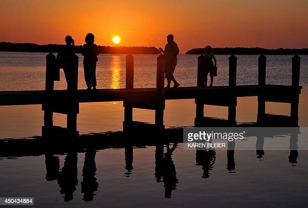 Tourists watch the sun set from a dock in Ilamorada in the Florida Keys February 24 2011 AFP PHOTO/Karen BLEIER