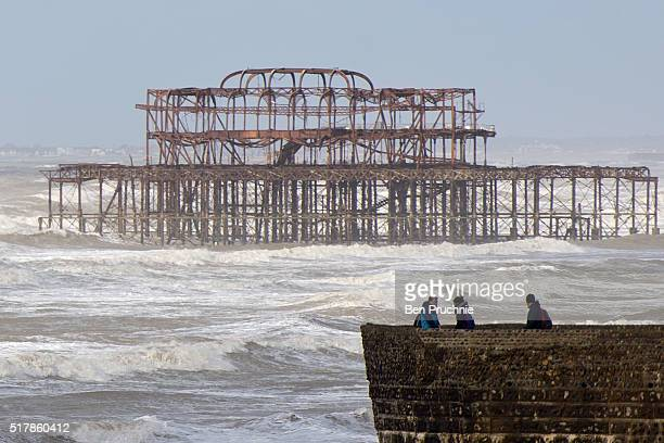 Tourists watch the waves on Brighton Beach on March 28 2016 in Brighton England Yesterday the Met Office issued an amber warning for winds for London...