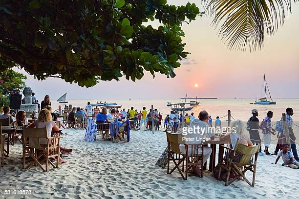 Tourists watching sunset  at restaurant on beach
