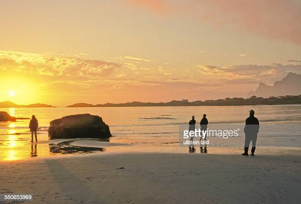 Tourists watching the midnight sun at the bay of Ramberg on the Lofoten islands Norway
