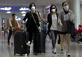 Tourists wear masks as a precaution against the MERS virus at the Incheon International Airport on June 6 2015 in Incheon South Korea Four deaths...