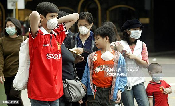 Tourists wear masks to protect themselves against a killer pneumonia on the streets of Hong Kong 30 March 2003 The outbreak of the killer pneumonia...
