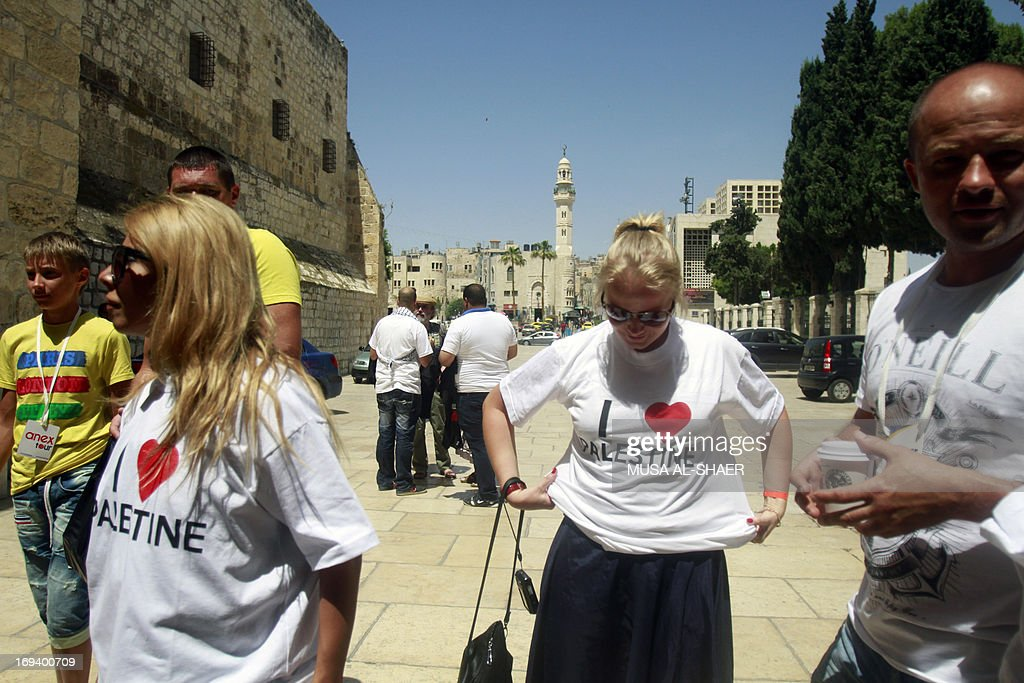 Tourists wear T-shirts reading 'I love Palestine' that they were offered by Palestinian youths as part of a campaign to raise awareness among foreign visitors about Palestinian indentity on May 24, 2013 in front of the Church of the Nativity in the West bank town of Bethlehem.