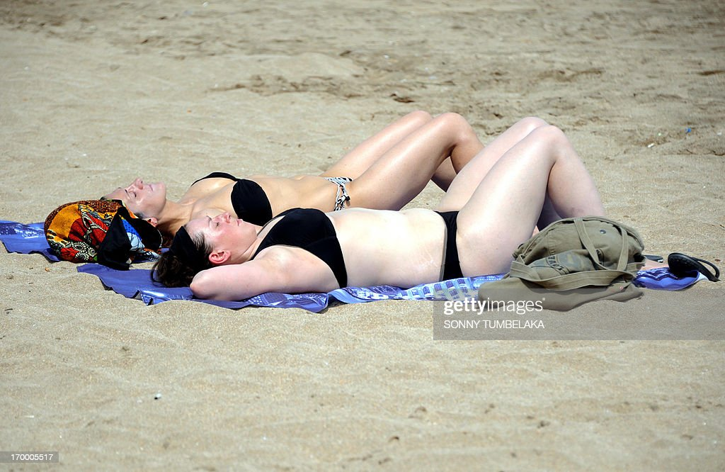 Tourists wearing bikinis lay on Kuta beach in Bali on June 6, 2013. Contestants at this year's Miss World beauty pageant will not wear bikinis in the parade in a bid to avoid causing offence in Muslim-majority Indonesia, organisers said on June 5, 2013.