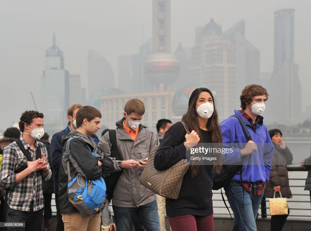 Tourists wearing breathing masks visit The Bund in the smog on January 3 2015 in Shanghai China The air quality index in Shanghai reached 230 in the...