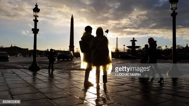 TOPSHOT Tourists wearing plastic Rain coats take à selfie in the sun after the rain at Place de la Concorde on February 4 2017 in Paris / AFP /...