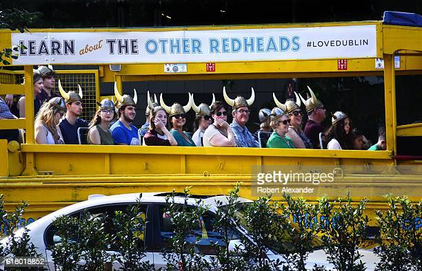 Tourists wearing plastic Viking helmets enjoy a tour of Dublin Ireland offered by Viking Splash Tours