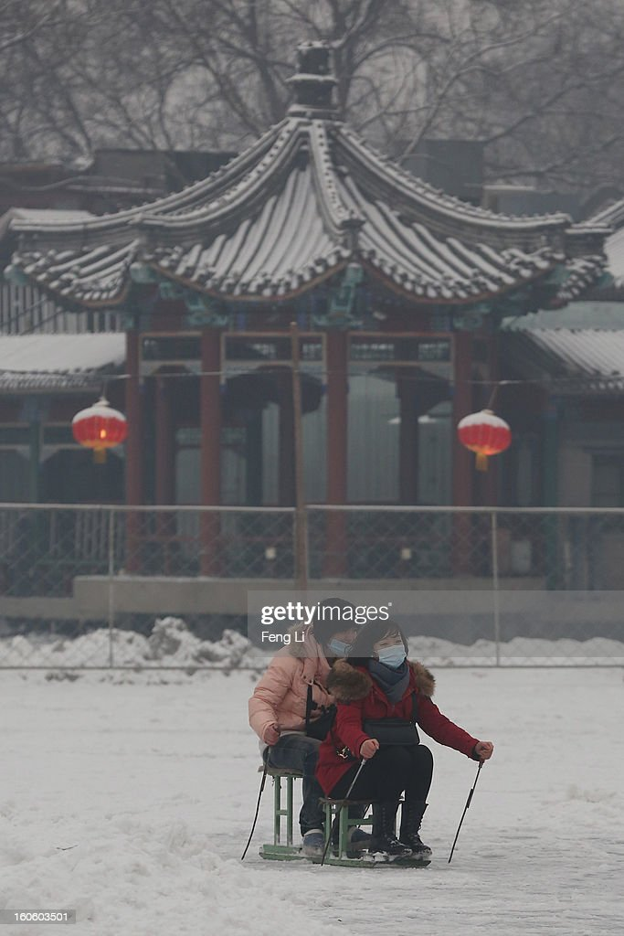 Tourists wearing the masks ride on specially constructed 'ice-chairs' on the frozen Houhai Lake during severe pollution on February 3, 2013 in Beijing, China. Houhai Lake is a popular place for winter sport and entertainment in Beijing.