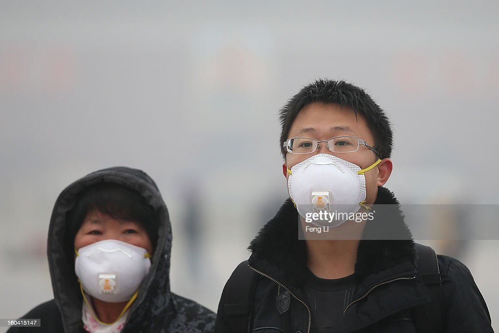 Tourists wearing the masks walk on the Tiananmen Square during severe pollution on January 31, 2013 in Beijing, China. Heavy smog that has choked Beijing for the last five days weakened slightly on Thursday due to a light rainfall, although the capital's air remains heavily polluted. The haze choking many Chinese cities covers a total area of 1.43 million square kilometers, the China's Ministry of Environmental Protection said Wednesday.