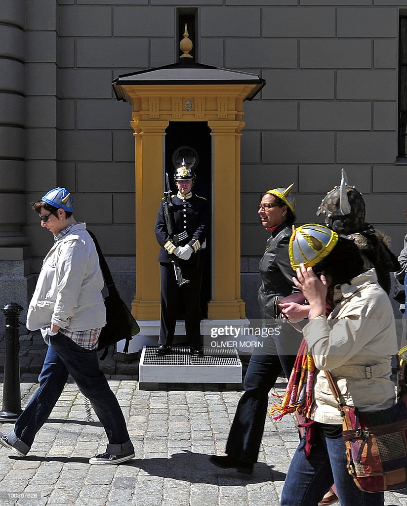 Tourists wearing Viking helmets pass by