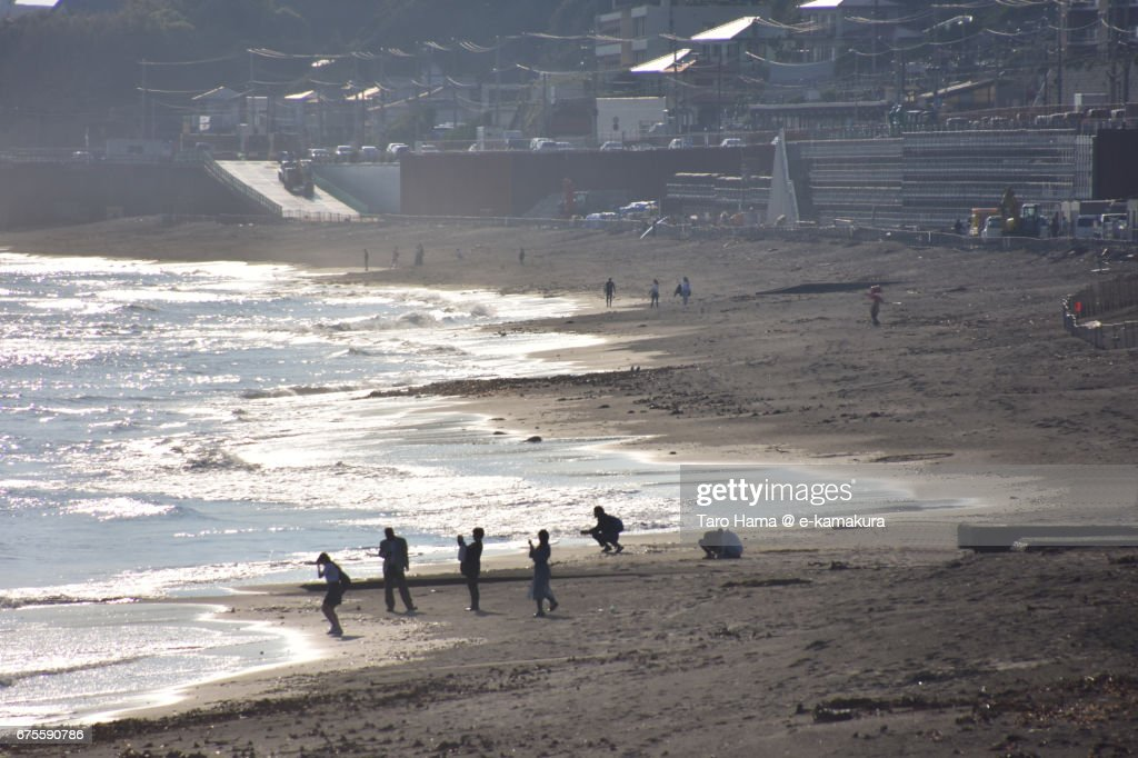 Tourists who take memorial photograph on the sunset beach : ストックフォト