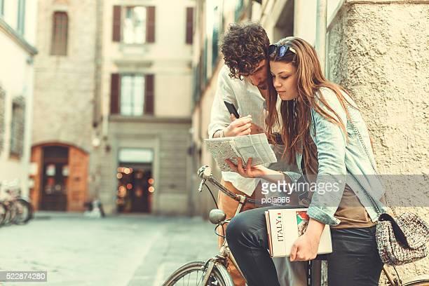 I turisti con guida e mappa di Italia nei vicoli