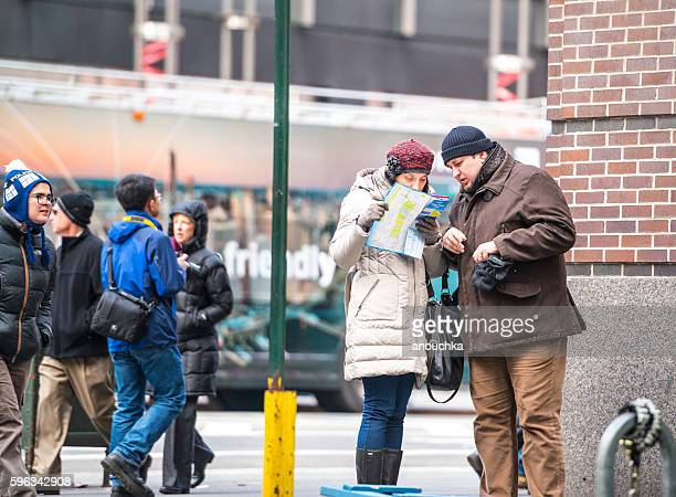 Tourists with NYC city map on Manhattan