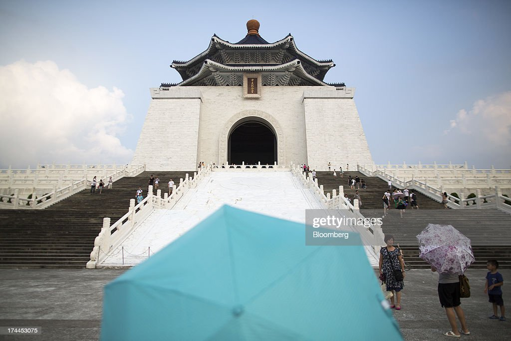 Tourists with umbrellas walk in front of the Chiang Kai Shek Memorial Hall in Taipei, Taiwan, on Wednesday, July 24, 2013. Taiwan President Ma Ying-jeou ruled out driving down the Taiwan dollar to boost exports following the currencys rally against the yen and said the government still aims for growth of at least 2 percent this year. Photographer: Jerome Favre/Bloomberg via Getty Images