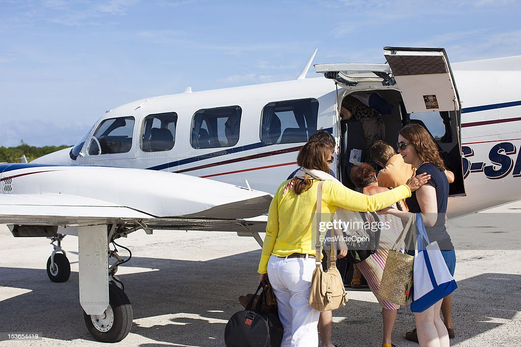 Tourists, young woman are boarding at a Piper, a private charter aircraft at Cat Island Airport on June 15, 2012 in Cat Island, The Bahamas.