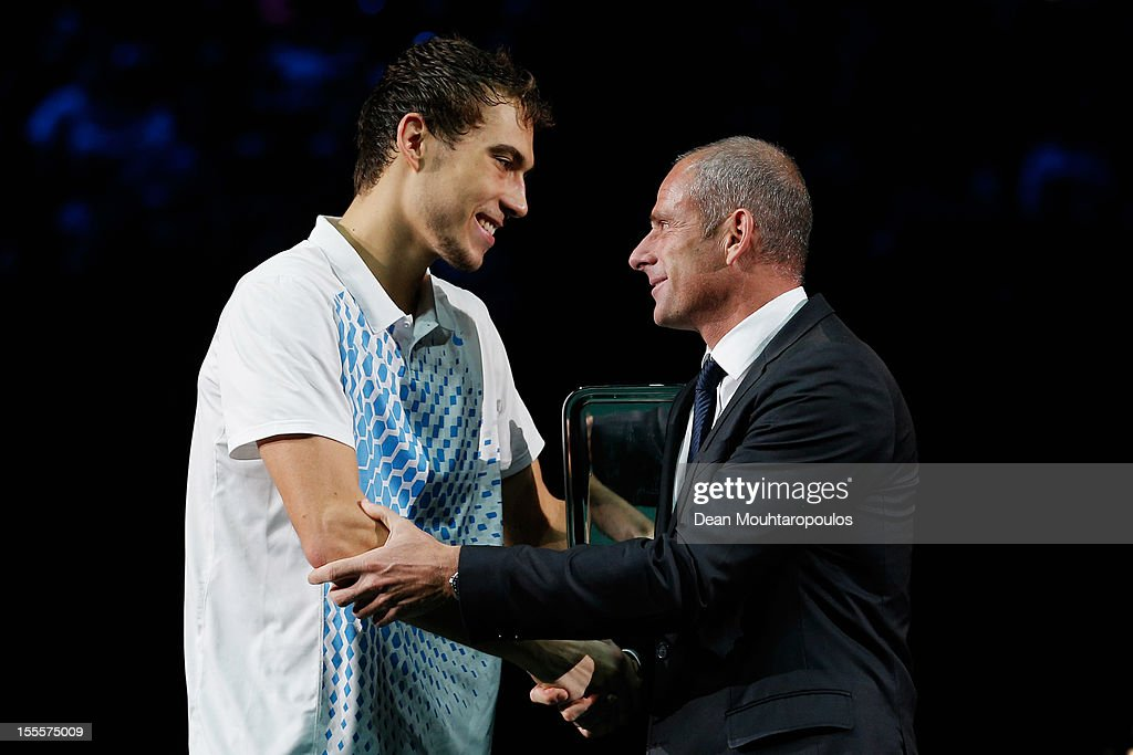 Tournament director for the BNP Paribas Masters Guy Forget hands Jerzy Janowicz of Poland the runners up trophy after defeat against David Ferrer of...