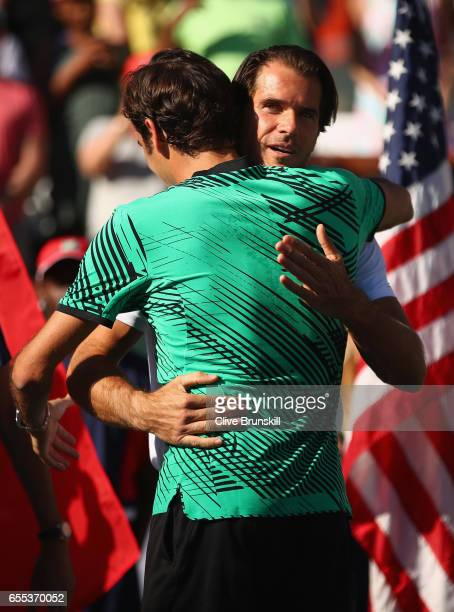 Tournament director Tommy Haas embraces Roger Federer of Switzerland after his straight sets victory against Stanislas Wawrinka of Switzerland in the...