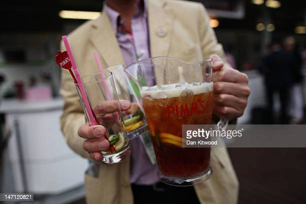 A tournament goer carries a jug of pimms on day one of the Wimbledon Lawn Tennis Championships at the All England Lawn Tennis and Croquet Club on...