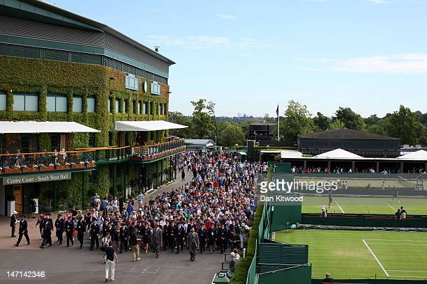 Tournament stewards escort the fans into the grounds on day two of the Wimbledon Lawn Tennis Championships at the All England Lawn Tennis and Croquet...