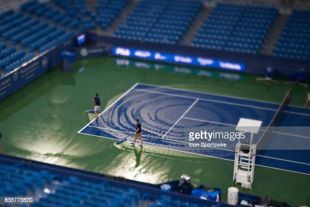 Tournament workers try to squeegee the tennis court after multiple rain delays during a match in the Western Southern Open at the Lindner Family...