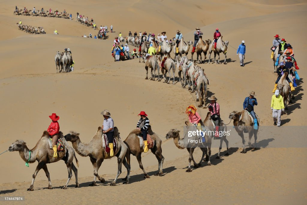 Toursits ride camels on a tour of Xiangshawan Desert also called Sounding Sand Desert on July 19 2013 in Ordos of Inner Mongolia Autonomous Region...