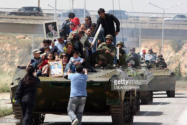 THIS PICTURE WAS TAKEN ON A GUIDED GOVERNMENT TOURSyrians holding up portraits of President Bashar alAssad ride on an army personnel carrier as...