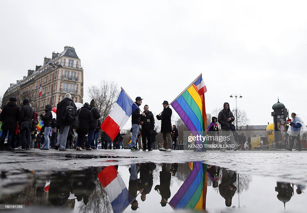 Tow men hold a French national flag and a rainbow flag as they gather to take the start of a demonstration for the legalisation of gay marriage and LGBT (lesbian, gay, bisexual, and transgender) parenting, in Paris on January 27, 2013, two days before a parliamentary debate on the government's controversial marriage equality bill, which will allow gay couples the same rights as their straight counterparts.