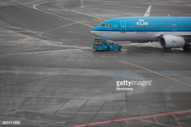 A tow tractor guides a passenger aircraft operated by KLM the Dutch arm of Air FranceKLM Group on the tarmac at Schiphol airport in Amsterdam...